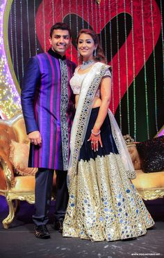 Sangeet Lehengas - Velvet Lehenga with Broad Mirror Work Silver Border | WedMeGood | Bride in a Lehenga with Morror Work, Diamond Jewelry and the Groom in a Vertically Striped Sherwani and Pants  #wedmegood #indianwedding #indianbride #lehenga #bridal #coupleshot #sherwani