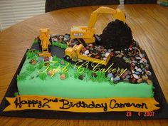 Construction Cake for Cameron! - 9x13 cake iced with traditional buttercream and covered with fondant.  Mini wondermold 'dirt' pile covered with crushed chocolate wafers.  Rocks are candy covered chocolate.  Vehicles are from DecoPac.