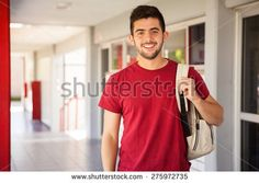 Portrait of a Hispanic college student carrying a backpack and standing in a school hallway - stock photo