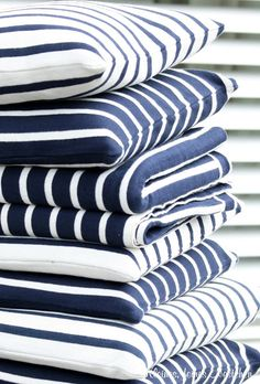 Crisp and clean striped pillows in coordinating shades of deep navy blue and white. Very nautical.