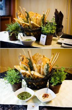 DIY Bread Basket with fresh baguettes, ficelle & grissini, topped with sea salt, pepper and rosemary in a basket surrounded by white bean dip, pesto and fresh herbs.