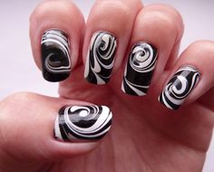 Create white swirling patterns for your water marble nail art design and paint them on your nails in contrast to a black base color and enjoy the results.