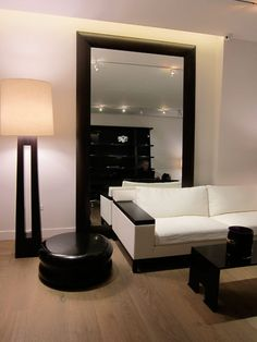 This vignette is classic Liaigre. The luxurious proportions of a giant mirror, framed in solid walnut, is used as a simple backdrop for a black-and-white composition featuring a Beluga sofa; a solid bronze Umberto coffee table, finished in waxed patina; a Dinka floor lamp; and the round Pulpe side table made of bronze.