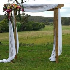 Rustic wedding arch. This timber wedding arch with draping white material looks fabulous on the farm. Dressed with bright coloured flowers. For more wedding arch inspiration and ideas you can visit us at www.ceremoniesido.com.au for all you wedding hire.
