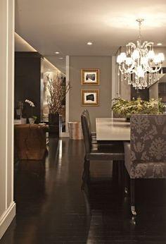 As duas cadeiras de cabeceira da mesa de jantar foram forradas com tecido adamascado do Empório Baraldin; as em couro são La Novitá. No piso, tábua corrida de ipê ebanizada