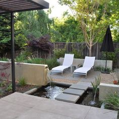 Small, modern yard with interesting placement of waterfall and water feature