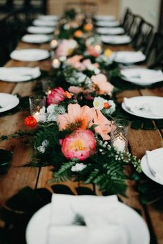 Orange hibiscus flowers + fern leaves create the perfect tropical table runner | Image by Gloria Goode Photography