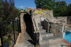 Thinking of adding kid-friendly features to your pool? A slide encased in a stone structure with steps and a tunnel with water falls is a fantastic way to keep it kid-friendly without your pool losing its grown-up look.