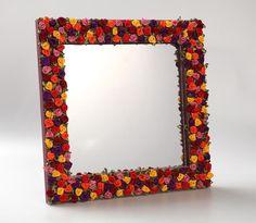 Espelho com moldura em MDF, com apliques em flores colorridas e fundo pintado.
