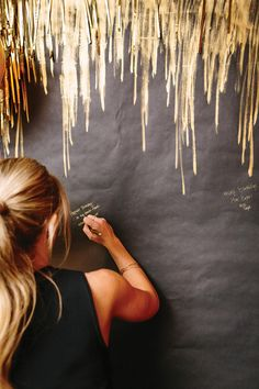Guests write their birthday wishes on a black paper wall with a gold ink pen