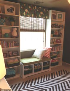Bookshelves in Baby Brady's room.  They are Ikea bookcases and window seat with custom window treatments, window seat and pillows.  Kinda love the brown chevron rug!