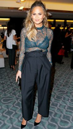 Chrissy Teigen in black paperbag-waist pants and a sheer green lace top
