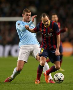 Edin Dzeko of Manchester City competes with Andres Iniesta of Barcelona during the UEFA Champions League Round of 16 first leg match between Manchester City and Barcelona at the Etihad Stadium on February 18, 2014 in Manchester, England.