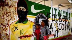ÍDOLO OCULTO. Las personas pasan delante de un graffiti que representa al futbolista Neymar con una capucha usada por miembros de grupos anarquista, contra de la Copa Mundial de Brasil 2014, en Río de...