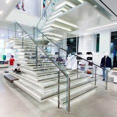 mcohenandsons @mcohenandsons Instagram photos | Painted Asymmetrical White Stair with Mirror-Polished Stainless Steel Accents and Custom LED Lighting at Lacoste in Manhattan