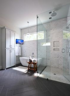 Transitional bathroom features a freestanding gray linen cabinet beside a tilted bathroom TV situated across from a glass sphere pendant over an oval tub under a wall mount tub filler. Bathroom with slate herringbone tile floors lead to the corner walk in shower featuring a marble subway tiles fitted stacked shower niches and a marble grid shower floor.