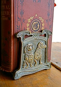 Adjustable book slide dating circa 1920s. Brass plated iron. Pair of dachshunds embossed on either side. Embossed 9780 on inside of each end