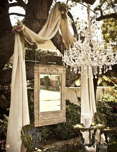 GORGEOUS use of fabric, mirror, and chandelier for an outdoor wedding altar