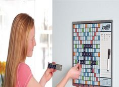 The Walk By Scrabble Board – This is a wall-mounted Scrabble game perfect for leisurely, ongoing contests with family members, co-workers, or roommates. The board's regulation surface is made of tin so the 100 magnetic tiles remain firmly affixed. Players can make a move whenever they walk by, and they store their letters on metal strips that hang from... #scrabbleboard #walkbyscrabbleboard