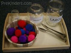 sorting small/medium/large pom-poms with tongs