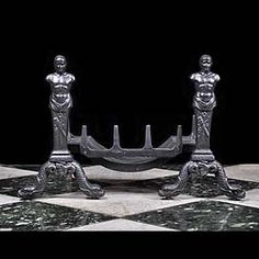 A PAIR OF CARRON CAST IRON MALE FIGURAL ANDIRONS in the Italian Mannerist style with Truscan warrior Caryatids and trophy adornment, the bases of intertwined sea serpents with the Falkirk Carron Foundry casting mark at the foot of each figure .  English mid 19th century.