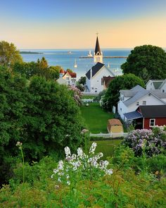 Mackinac Island + Michigan ...  This picture really intrigues me:  in addition to being just plain beautiful, the skyline and church and man-made parts in general look  like a painting to me, while the trees and natural parts in the foreground look like a photograph...