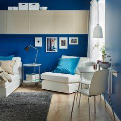 Espaço de refeição numa sala com uma mesa rebatível para parede em branco combinada com duas cadeiras em branco com pernas em aço inoxidável