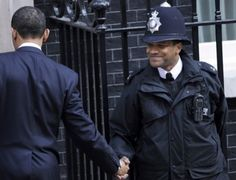 """""""This is the most powerful photo in the series. Remember they are not supposed to shake hands, but the two brothers couldnt resist the historic moment. The police guard never imagined in his wildest dream that he would usher a black American president into the British corridors of power."""" #BarackObama"""