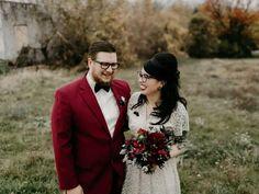 Groom wearing burgundy wedding suit and bride wearing vintage lace dress