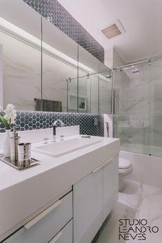 O banheiro branco é um clássico, não é? O diferencial desse espaço fica por conta do revestimento sextavado e do espelho retro iluminado.