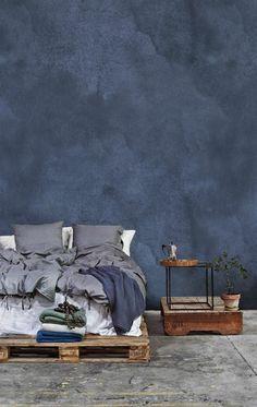 Schlafzimmer mit grau blauer Wand, Doppelbett aus Europaletten, graue Schlafdecke