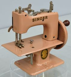 Toy Singer Sewing Machine. This Singer model was produced sometime between 1914 and 1922.It's often difficult to determine whether the better-made small sewing machines at the turn of the century really were intended as toys for children or for use by adults. These toy machines were nicely made and functioned very well, sewing a simple chain stitch in most cases. In the post-Second World War era, metal gave way to plastic construction for many children's toys. #sewing #toy #pink