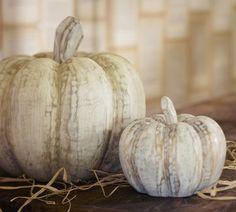 Whitewashed wood pumpkins create rustic charm.