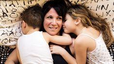 Eine Mutter liegt zusammen mit ihren Kindern in einem Bett und kuschelt.