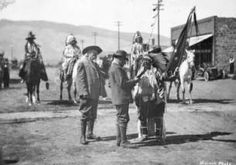 "William F. Cody and Prince Albert I of Monaco speak with Chief Plenty Coups on Sheridan Avenue in Cody, Wyoming. Chief Plenty Coups and four mounted Native Americans are in traditional regalia. Cody holds a rifle Prince Albert I presented to Chief Plenty Coups. Chief Plenty Coups holds his personal flag. Typed caption on mat, ""Albert, Prince of Monaco, on a 1913 hunt in the Cody Country visits with his host Buffalo Bill and Indian members of the party on Cody's main street""."