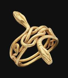 A GRAECO-ROMAN GOLD SNAKE RING  CIRCA 1ST CENTURY B.C.-1ST CENTURY A.D.  Composed of two coiling snakes, their heads turned out on either side, their bodies forming a Herakles knot at the centre, details incised.