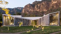 Cadaval & Sola-Morales has used stone walls, a swooping concrete roof and large expanses of glazing to frame mountain views retreat outside of Mexcio City.