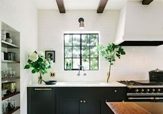 {The black window frames add to the contrasts in this beautiful kitchen. Helgerson used Granada Tile's Badajoz cement tiles in black and white along with a La Canche range, and a pair of Boston Hanging Pendants in Hand-Rubbed Brass from Circa Lighting.}