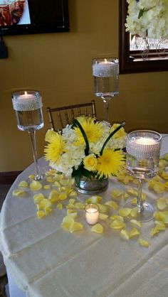 Glass cylinder arranged with white hydrangea, yellow spider mums and yellow roses accented with Monkey Grass and surrounded with rose petals.  DorisTheFloristt.com