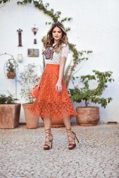 Look Tássia Naves com saia midi laranja e blusa bege