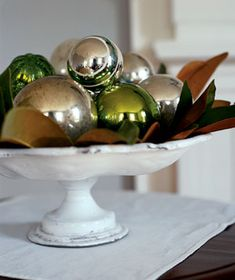 Place vintage ornaments on a cake stand nested with leaves for a stunningly simple centerpiece