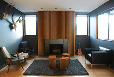 Crisp dark walls make the Douglas fir slats around the fireplace pop. Photo by Zen Sekizawa