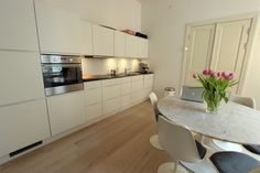 Tulip dining table & chairs. White modern kitchen.