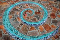 https://flic.kr/p/83iTDL | Mosaic Swirl - 2006 | This is the size of a small helicopter landing pad and was actually meant to be one in case of an emergency.  There were several people that worked on the project.  My friend Fe McQueen did a sketch for us which we loosely based the swirl on.   A thin arrow that bissected the entire work was eliminated  - all that remains of that  line are the nuggets of red glass at the center of the spiral.  Thanks for the great comments!