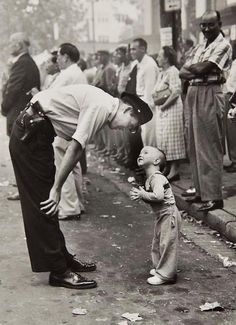 """William C. Beall - """"Faith and Confidence"""": A policeman speaks to a young boy at a parade in Washington, D.C., 1958. Pultizer Prize for Photography."""