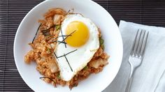 The spicy tang of kimchi (sometimes spelled kimchee) gives a delicious Korean twist to fried rice. Top each bowl with a sesame oil-fried egg to make it a complete meal.