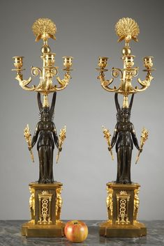 Early 19th century pair of patinated and gilt bronze three-light candelabra - An exceptional Empire pair of candelabras in gilded and patinated bronze, with three arms of light richly decorated with griffons, palmette and scrolls disposed symmetrically around a centra