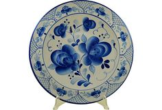 Hand-painted Russian ceramic plate with a flower design in blue on a white background.