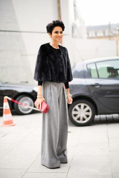 In a short fur cape and wide leg pants.