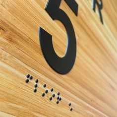 Braille signage printed on wood veneer using primer and clear gloss printed inline with black and white inks to build texture on the LogoJET UV2400 printer.
